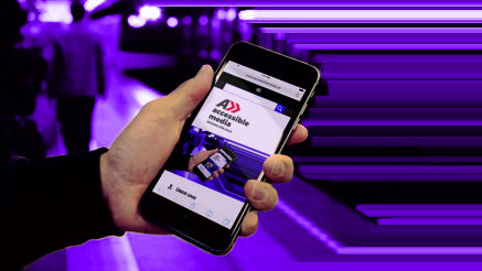 Hand mit Smartphone und accessible media Website im Viewport in einer U-Bahn-Station